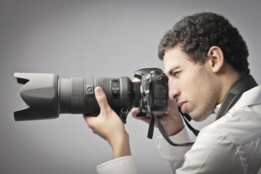 Young african man taking pictures with a reflex camera